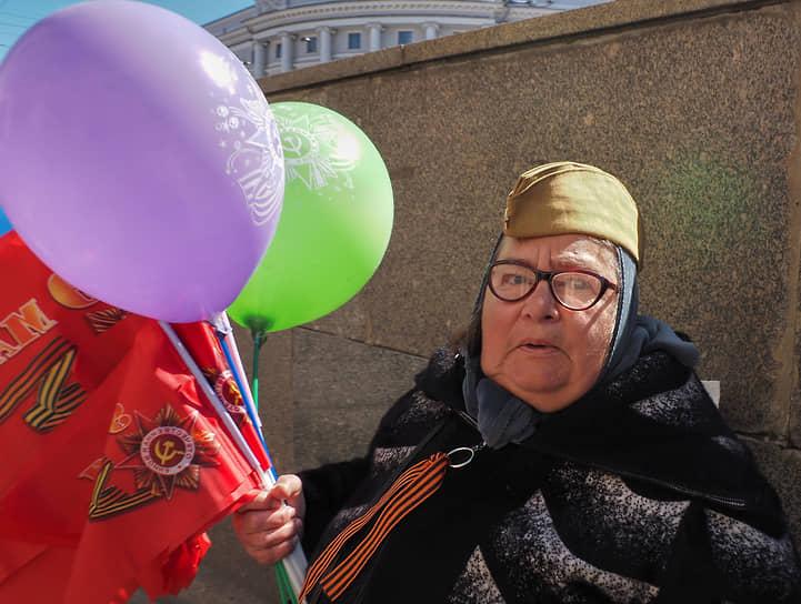 Пожилая женщина продает красные флажки и воздушные шары на Невском проспекте