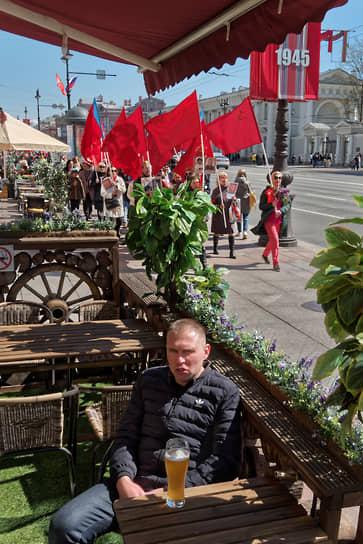 Молодой человек пьет пиво в уличном кафе на Невском проспекте на фоне людей с красными флагами