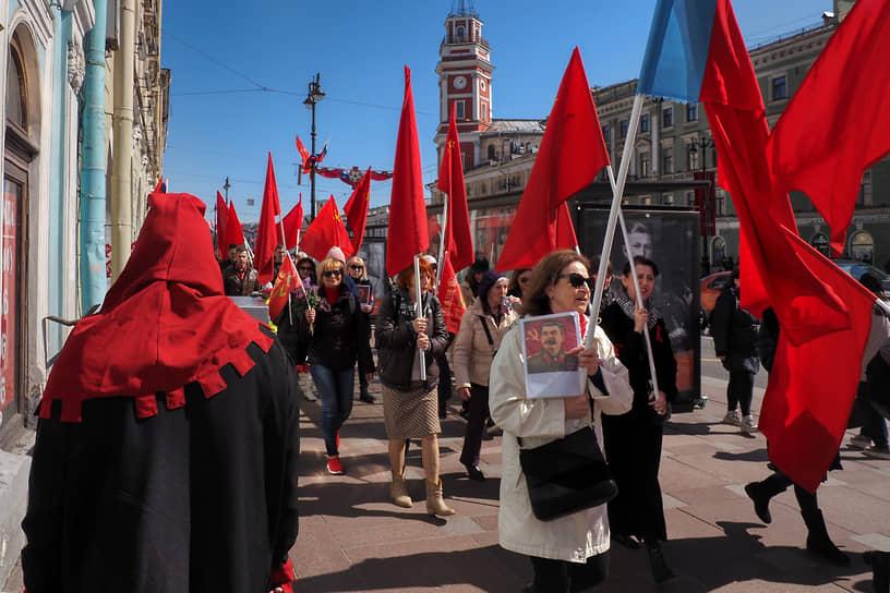 Люди с красными знаменами и портретом Сталина идут по Невскому проспекту