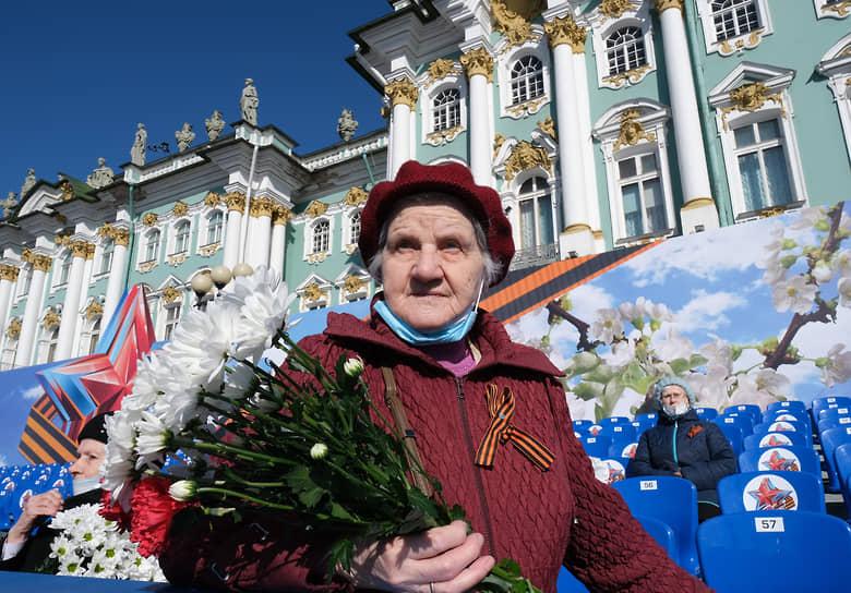 Бабушка-ветеран с цветами на гостевой трибуне во время парада