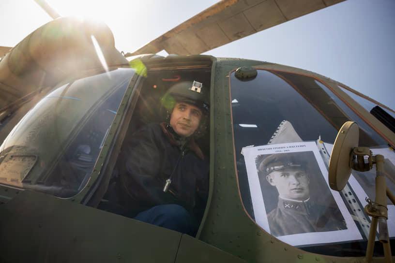 Пилот Военно-воздушных сил (ВВС) в кабине вертолета с портретом героя войны Трофима Щебетина перед началом парада