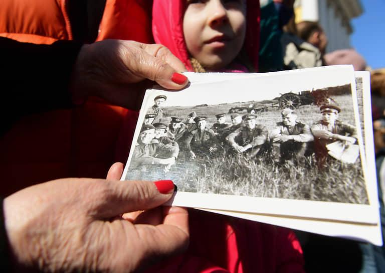 Женщина держит показывает фотографию своего отца, участника Великой Отечественной Войны, во время Парада на Дворцовой площади