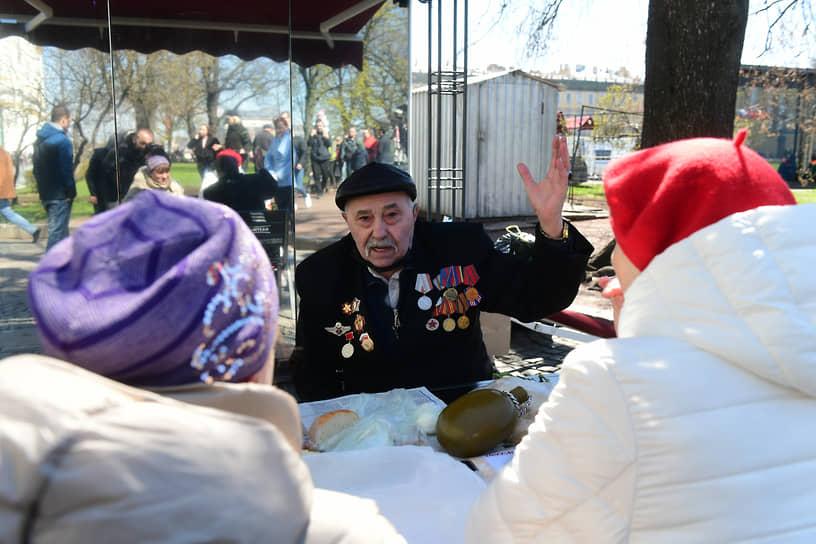 Пожилой мужчина с медалями в кафе на Дворцовой площади после Парада Победы