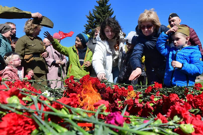 Горожане кладут цветы к вечному огню в центре памятника «Борцам революции» на Марсовом поле
