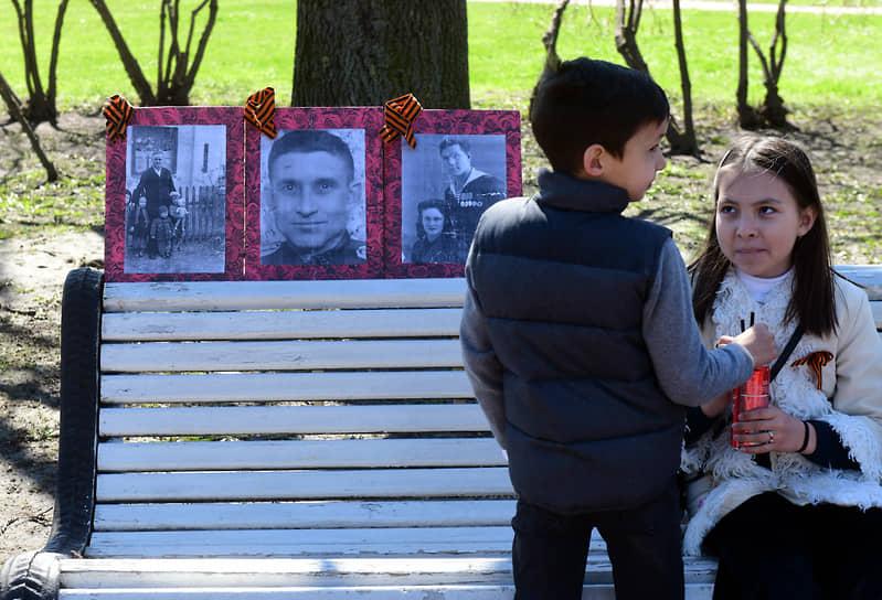 Мальчик с девочкой на скамейке на фоне портретов родственников в день празднования Дня Победы на Марсовом поле