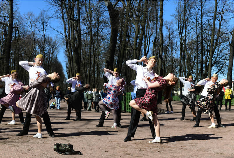 Молодые люди танцуют в Летнем саду в День Победы
