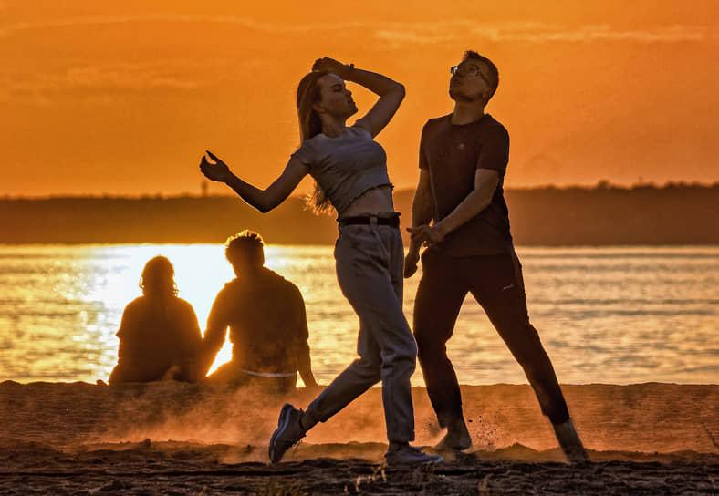 Девушка и парень танцуют на на берегу Финского залива