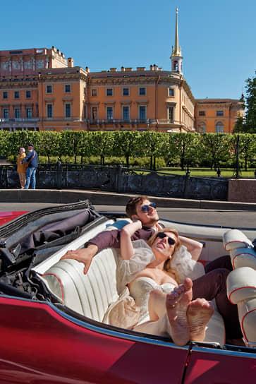 Молодые люди в образе жениха и невесты в кабриолете на фоне Инженерного замка
