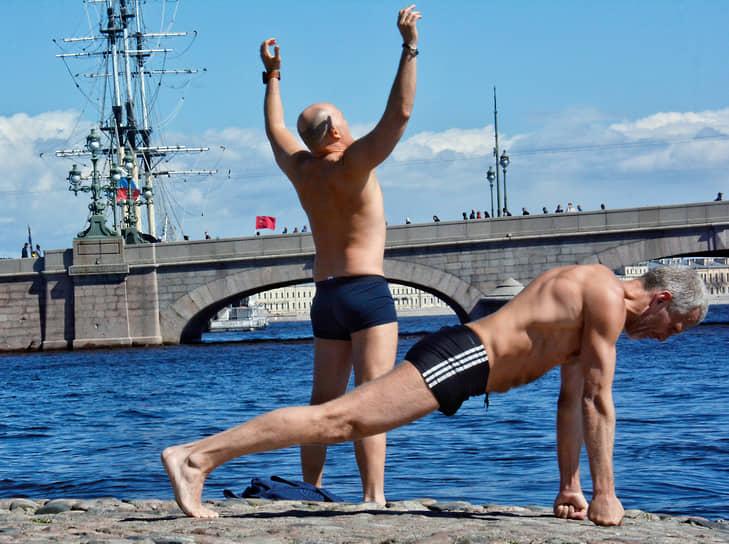 Мужчины занимаются физическими упражнениями на пляже Петропавловской крепости