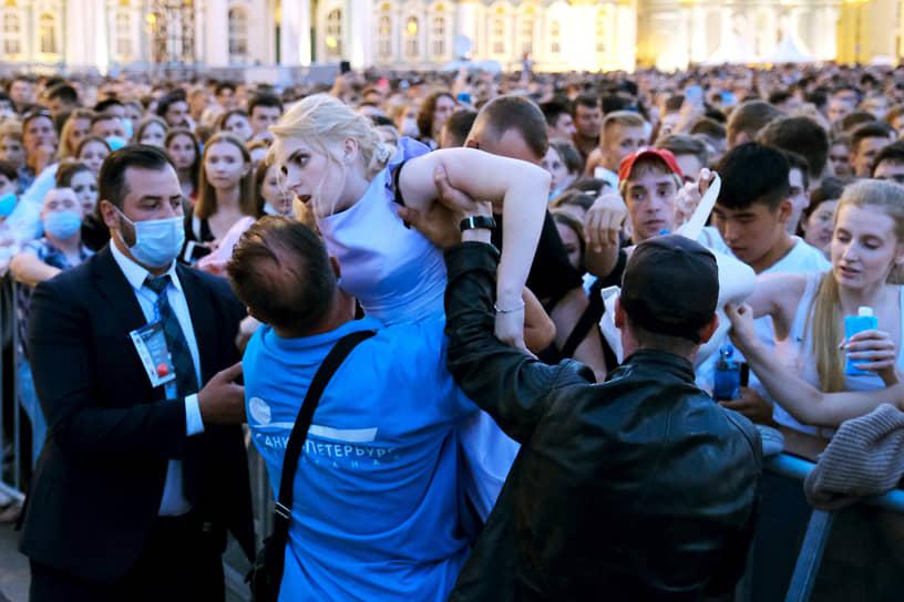 Выпускники на Дворцовой площади во время праздничного концерта. Сотрудники охраны помогают девушке выбраться из толпы