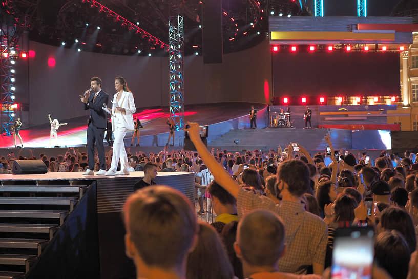 Выпускники во время праздничного концерта на Дворцовой площади. Ведущие концерта Иван Ургант и Дарья Александрова