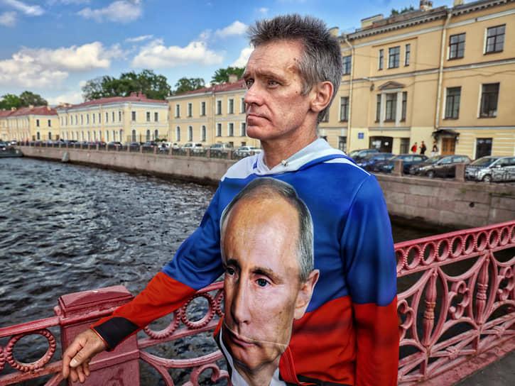 Мужчина в толстовке с портретом президента России Владимира Путина в центре города