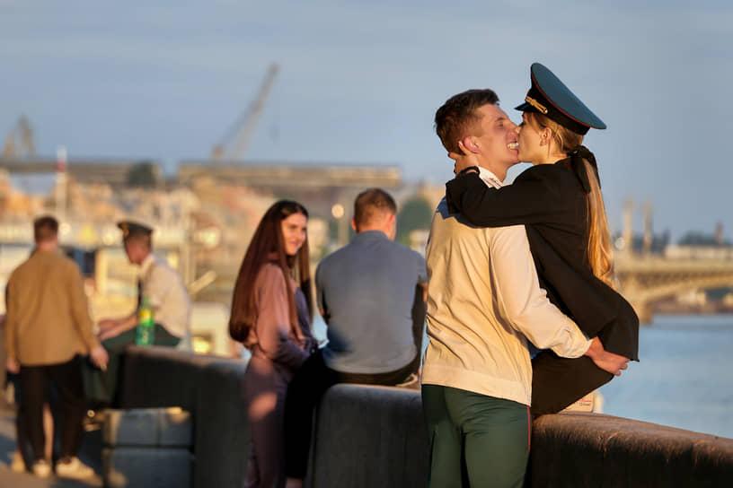 Молодые люди целуются на набережной