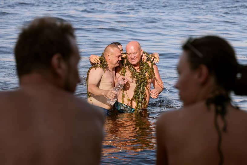 Мужчины купаются во время жары