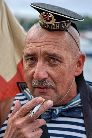 День Военно-морского флота (ВМФ). Мужчина в тельняшке и в шуточной бескозырке курит на набережной Невы