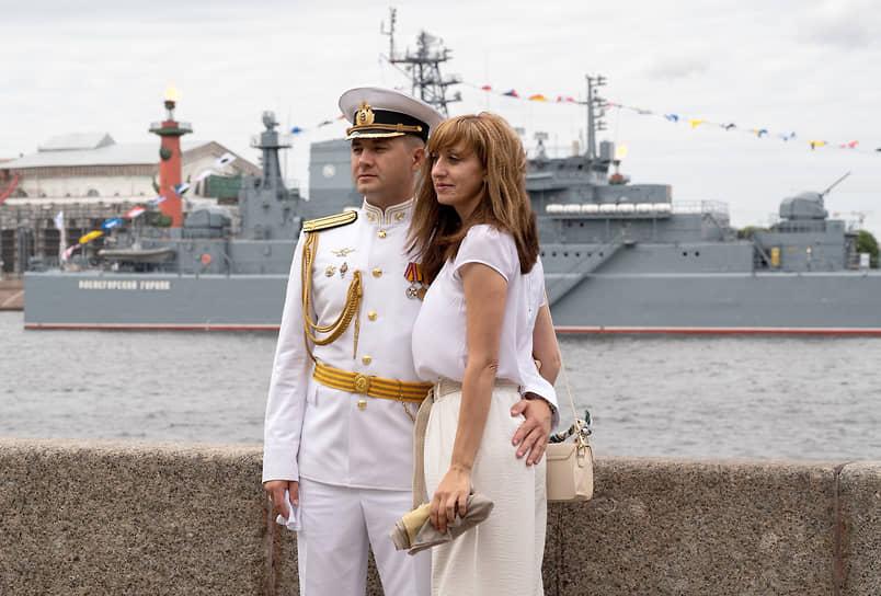 Празднование Дня Военно-морского флота (ВМФ) России. Молодые люди на набережной на фоне военного корабля