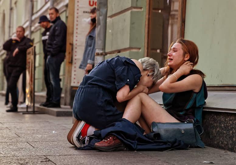 Две девушки сидят на тротуаре