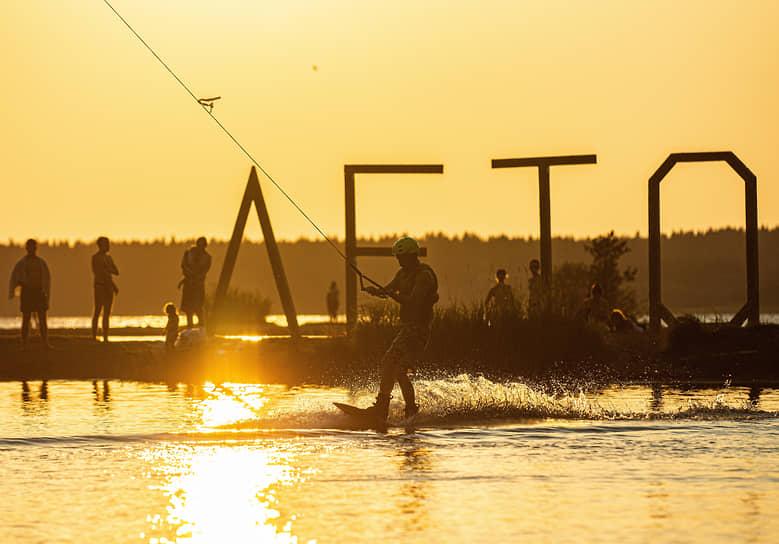 Мужчина занимается вейксёрфингом на озере