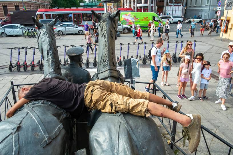 Молодой человек лежит на памятнике петербургской конке на Васильевском острове