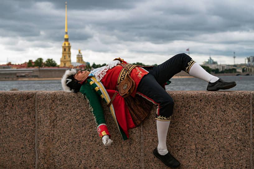 Уличный актер в историческом костюме лежит на парапете набережной