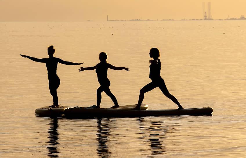 Жители города занимаются йогой на сап-досках на Финском заливе