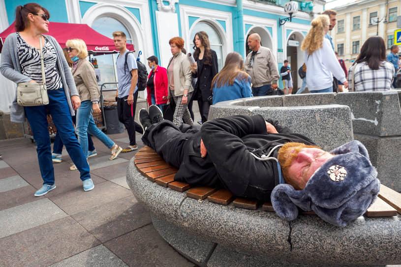 Мужчина в шапке ушанке спит на скамейке на набережной канала Грибоедова