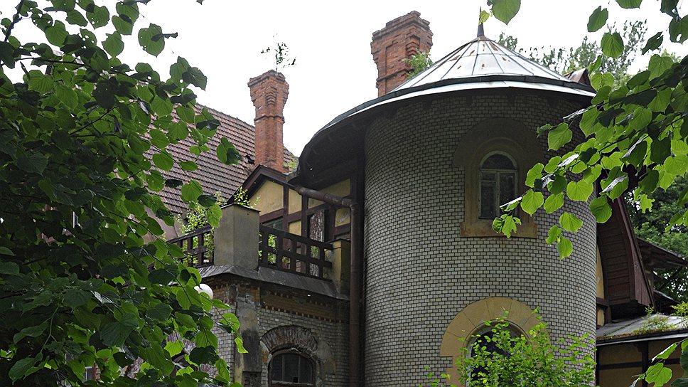 Угловая полукруглая каменная башенка с полуциркульными окнами делает этот дом похожим на маленький замок