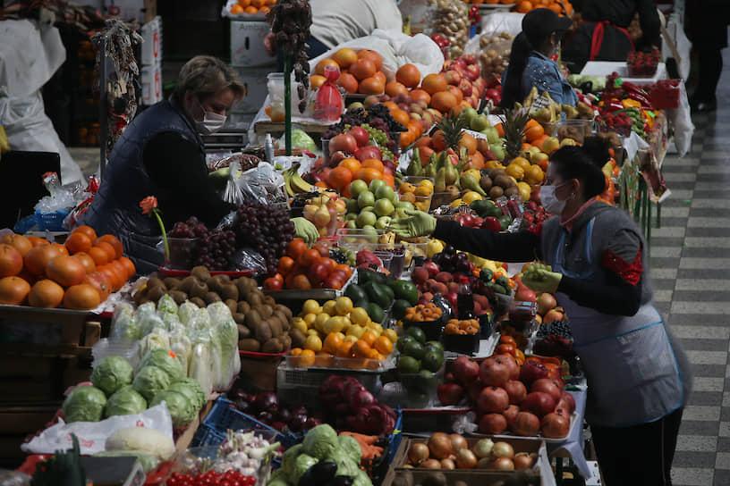 Продавщицы овощей в медицинских масках на рынке