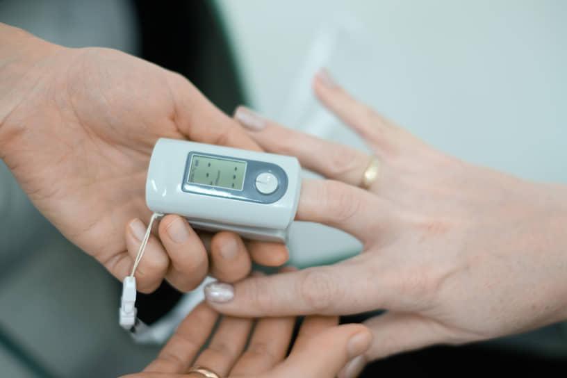 """Вакцинация от коронавирусной инфекции COVID-19 вакциной Гам-КОВИД-Вак (""""Спутник V""""). Жанровая фотография. Медицинский сотрудник в мобильном пункте вакцинации во время измерения уровня кислорода в крови пациента. Пульсоксиметр на пальце пациента"""