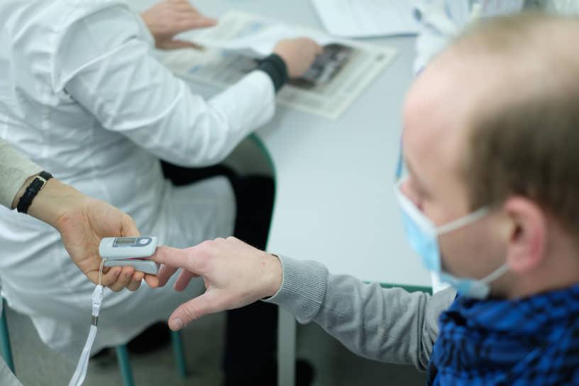 """Вакцинация от коронавирусной инфекции COVID-19 вакциной Гам-КОВИД-Вак (""""Спутник V""""). Жанровая фотография. Медицинский работник в мобильном пункте вакцинации во время вакцинации пациента"""