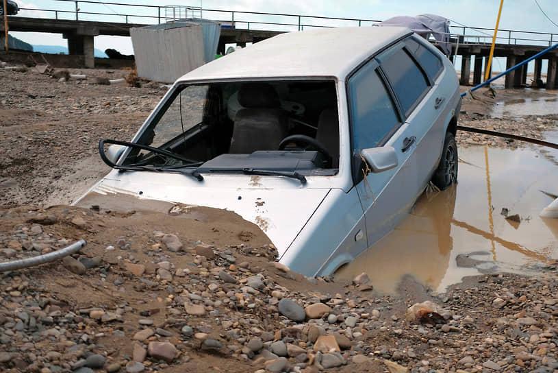 Июль 2021 г. Россия, Краснодарский край, Туапсинский р-он Последствия наводнения в Лермонтове. Затопленная водой и песком территория пляжа. Автомобиль ВАЗ-2109 под песком на пляже.