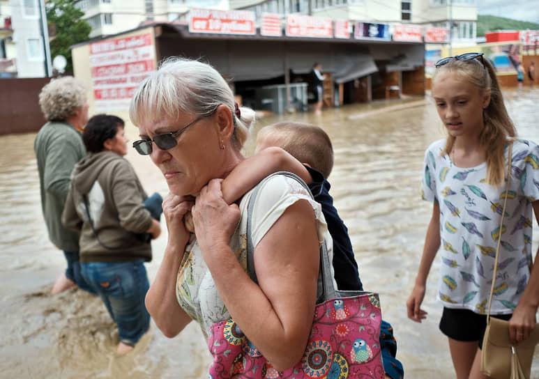 Июль 2021 г. Россия, Краснодарский край, Туапсинский р-он Последствия наводнения в Лермонтове. Затопленная водой улица поселка. Туристы после наводнения идут по колено в воде.