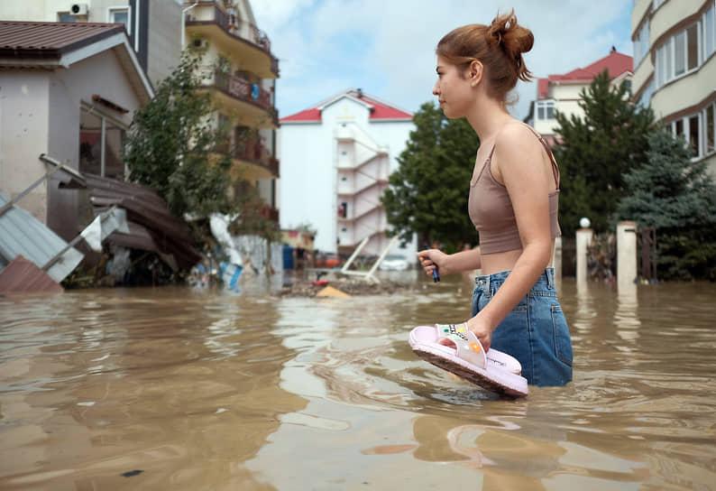 Июль 2021 г. Россия, Краснодарский край, Туапсинский р-он Последствия наводнения в Лермонтове. Затопленная водой проезжая часть. Девушка туристка идет по пояс в воде на фоне гостиниц.