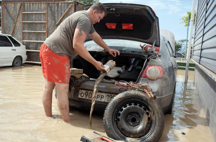 Июль 2021 г. Россия, Краснодарский край, Туапсинский р-он Последствия наводнения в Лермонтове. Затопленная водой территория двора жилого дома. Турист выливают воду из своей машины после наводнения.