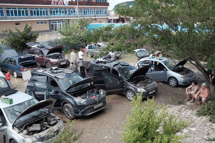 Июль 2021 г. Россия, Краснодарский край, Туапсинский р-он Последствия наводнения в Лермонтове. Автомобили туристов с открытыми капотами у гостиницы после наводнения.