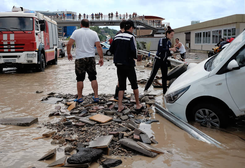 """Июль 2021 г. Россия, Краснодарский край, Туапсинский р-он Последствия наводнения в Лермонтове. Затопленный водой участок трассы """"Джубга - Сочи"""" и выброшенный потоком воды на разделительное ограждение автомобиль."""