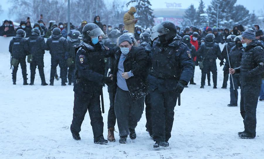 Трое стражей порядка сопровождают задержанного протестующего