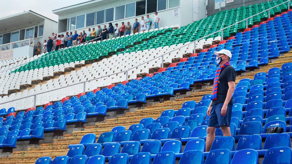 Немногочисленные болельщики спрятались от дождя под навесом, а фанат хабаровской команды внимательно следит за игрой, будто не замечая осадков.