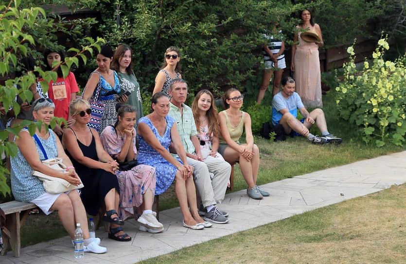Публика укрылась от жары в тени.