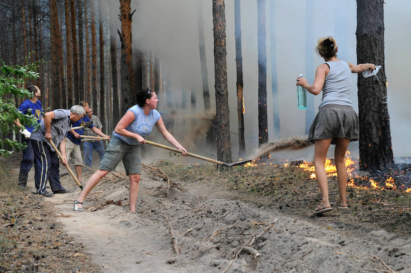 На фото: отдыхающие лопатами, песком и водой из пластиковых бутылок тушат горящий лес на подступах к турбазе «Коминтерновец» под Воронежем