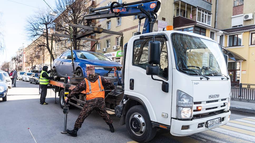 Сотрудники частной компании по эвакуации автомобилей (работает вместе с ГИБДД) грузят неправильно припаркованную в Воронеже машину на эвакуатор