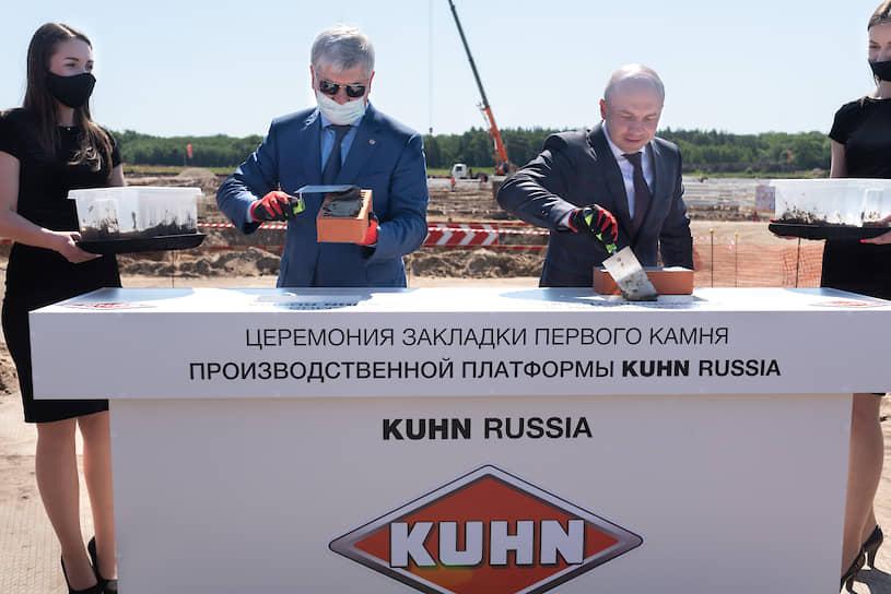 Господа Гусев и Манзюк уложили именные кирпичи в стенд, стоящий перед котлованом стройплощадки