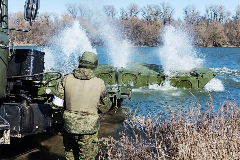 Учебно-тренировочные занятия по наведению паромной переправы инженерным подразделением в Воронежской области. Военные сбрасывают сложенное звено понтона с грузовика в реку. Через секунды оно само развернется в воде