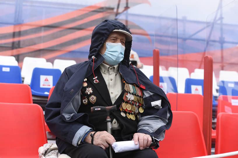 Один из зрителей парада Победы в Воронеже. В целях борьбы с распространением коронавируса на трибунах между креслами установили пластиковые экраны