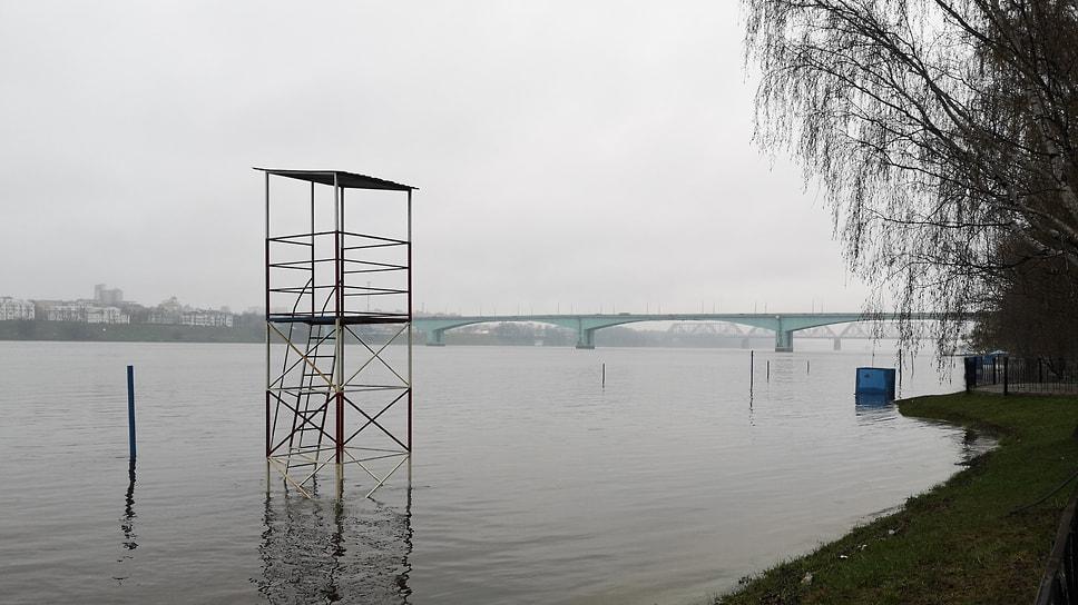Затопленная волейбольная площадка Тверицкого пляжа на фоне Октябрьского моста.