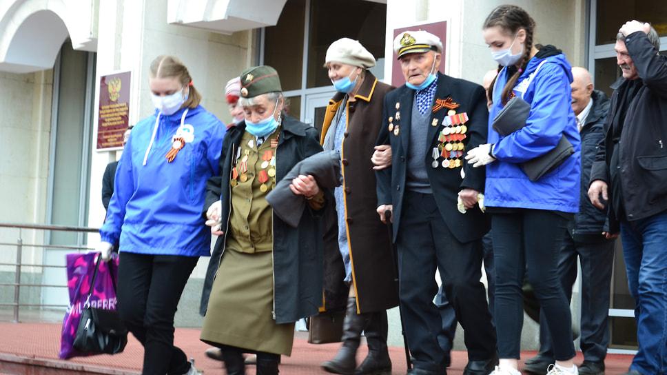 Волонтеры помогают ветеранам Великой Отечественной войны спуститься с лестницы.