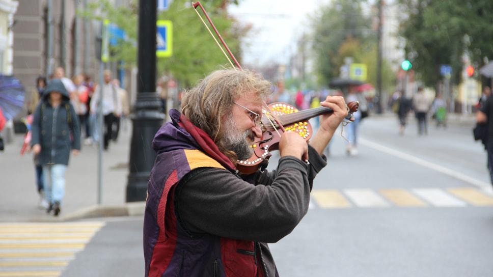 Уличный скрипач во время дождя