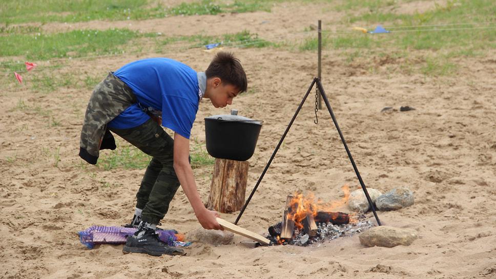 Мальчик поддерживает огонь костра для ухи