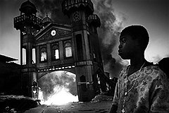 """Рикардо Вентури (Contrasto). """"Девочка смотрит, как горит старый Железный Рынок. Порт-о-Пренс, Гаити, 18 января 2010 года"""". Первое место в категории """"События. Одиночные фотографии"""""""