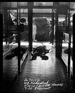 Вермонт-стрит, 768. Мертвое тело в выложенном плиткой коридоре, на заднем плане полицейские поднимают простыню. 1932 год. Фотограф: Маннз